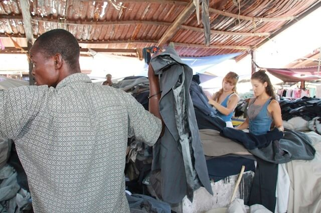 Local Buttons sourcing materials at a second-hand clothing market in Haiti