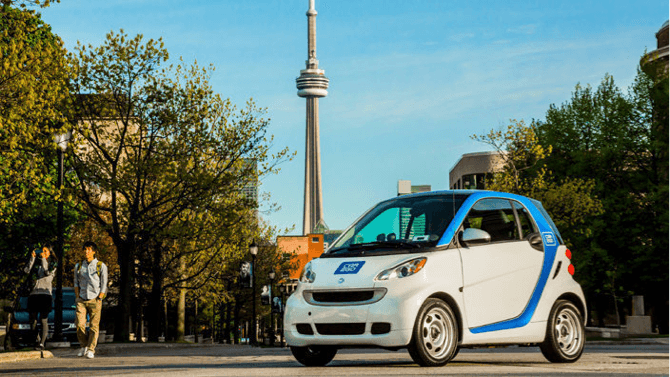 a car2go electric smart car with the CN tower in the background