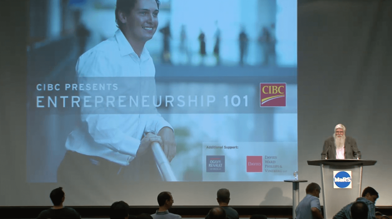 Tony Redpath speaks at the podium at an Entrepreneurship 101 lecture in 2008. An Entrepreneurship 101 image shows in the background on an overhead screen.